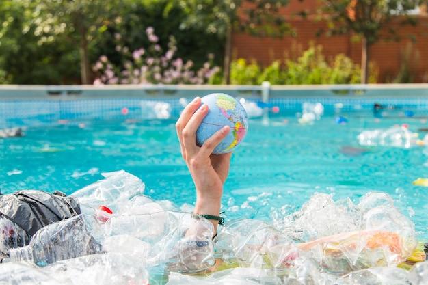 Ufa, rússia - 25 de julho de 2019: problema de lixo, reciclagem de plástico, poluição e conceito ambiental - poluição de lixo de plástico em ambiente aquático, globo terrestre está flutuando no lixo.