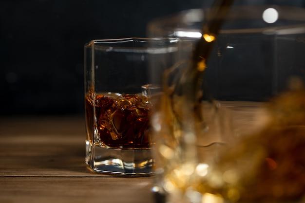 Uísque bebe na madeira com cubos de gelo e respingo.