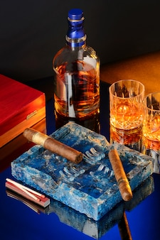 Uísque, charutos e cinzeiro na mesa de madeira