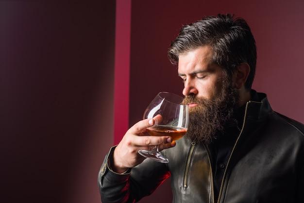 Uísque com álcool forte e homem brutal bebe degustação de uísque e homem com gosto de sommelier em couro