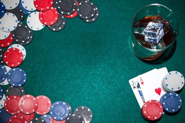 Uísque com cubos de gelo e fichas de casino e cartão de jogo na mesa de poker verde