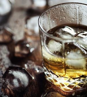 Uísque com gelo com um copo. cubos de gelo em uma mesa de madeira e um copo com álcool forte gelado. mesa com whisky americano, bourbon e cartas. Foto Premium