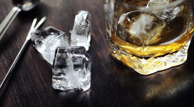 Uísque com gelo com um copo. cubos de gelo em uma mesa de madeira e um copo com álcool forte gelado. mesa com whisky americano, bourbon e cartas.