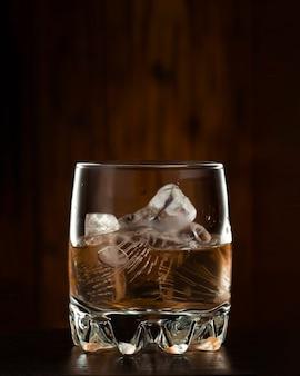 Uísque com gelo em um fundo escuro de madeira.