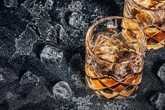 Uísque com gelo em um fundo escuro de pedra.
