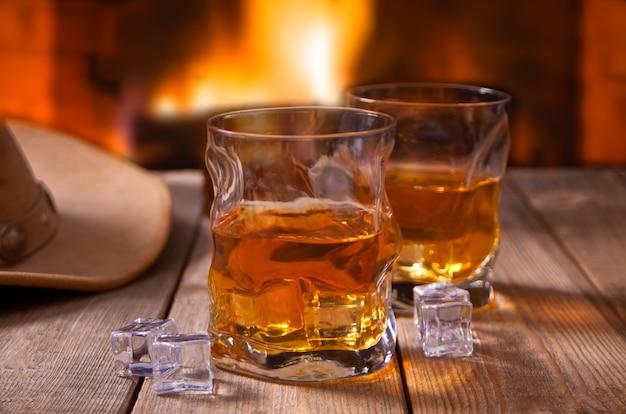 Uísque com gelo em uma mesa de madeira com lareira e chapéus de cowboy
