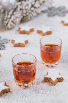 Uísque, conhaque ou licor, biscoitos e decorações do feriado de inverno em fundo branco. conceito de férias sazonais.