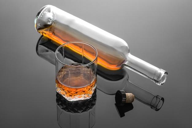 Uísque derramado em um copo na atmosfera fria e cinza, hora de relaxar com o uísque.