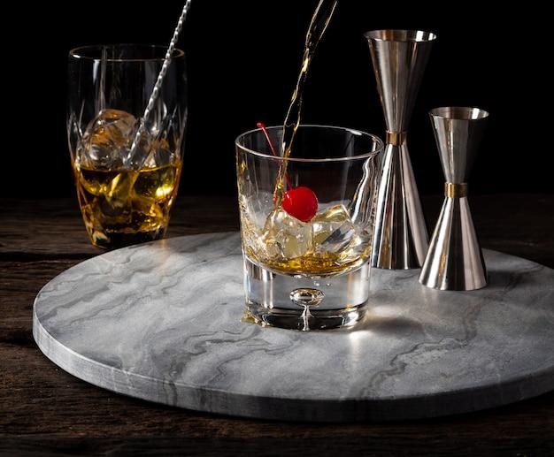 Uísque derramando em vidro com cereja e jigger bartender