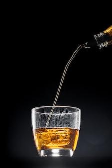 Uísque, despejando um copo no preto