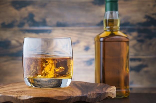 Uísque dourado com cubos de gelo na mesa de madeira com garrafa de uísque ou uísque.