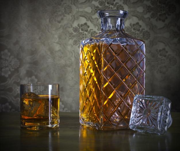Uísque em garrafa e copo com gelo