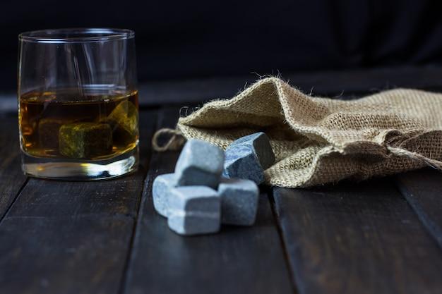 Uísque em um copo com pedras para refrescar bebidas em uma mesa de madeira