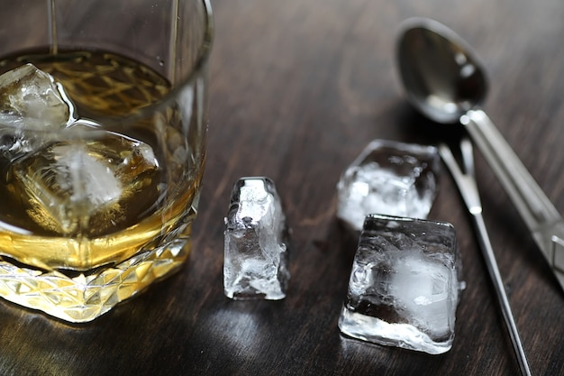 Uísque em um copo e pedaços de gelo em uma mesa de madeira
