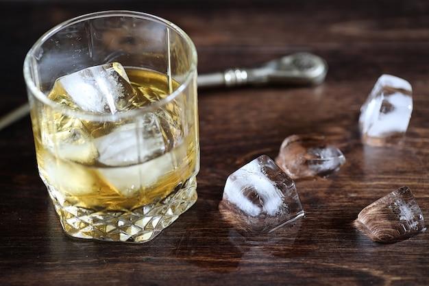 Uísque em um copo e pedaços de gelo em uma mesa de madeira Foto Premium