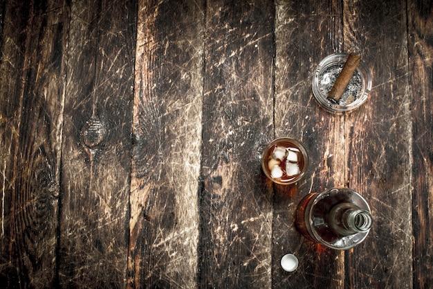 Uísque escocês com charuto. sobre um fundo de madeira.