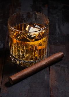 Uísque escocês de single malte em copos de cristal com cubos de gelo e charuto cubano na superfície da mesa de madeira.