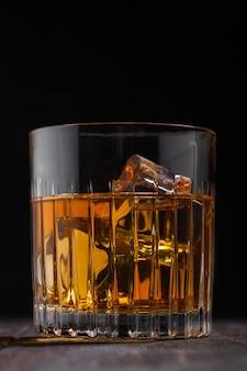 Uísque escocês de single malte em vidro de cristal com cubos de gelo na superfície da mesa de madeira. macro