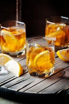 Uísque frio com gelo e limão em cima da mesa vintage