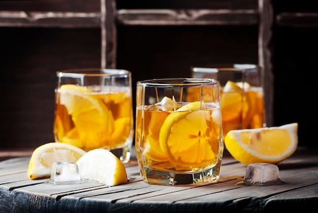 Uísque frio com gelo e limão na mesa de madeira