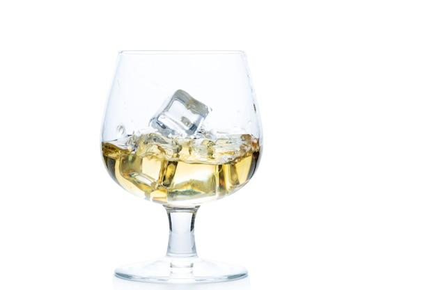 Uísque ou conhaque com gelo no copo de snifter ou balão isolado no fundo branco, conceito de bebida