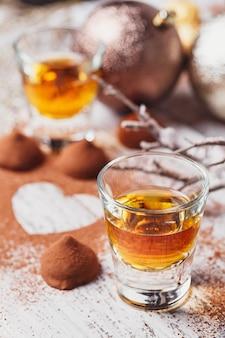 Uísque ou licor, bombons de trufa de chocolate no cacau em pó e decorações de natal em fundo branco de madeira.