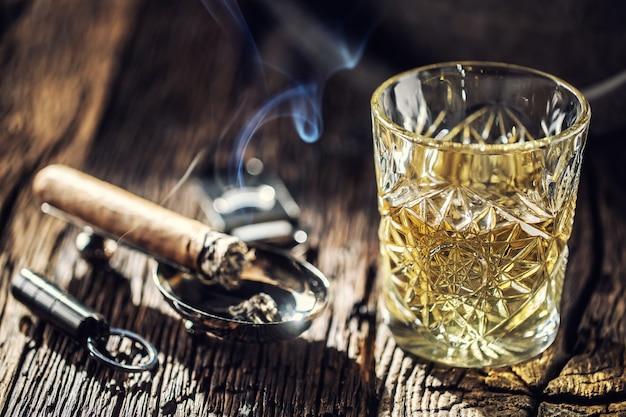 Uísque sem gelo em uma xícara com charuto aceso e um velho barril de madeira no fundo.