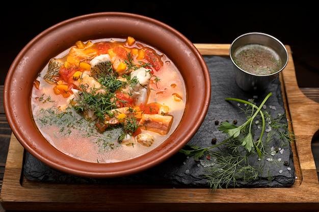 Ukha regiamente, sopa de peixe, de diversas variedades de peixes, em um prato de barro, sobre uma tábua de madeira