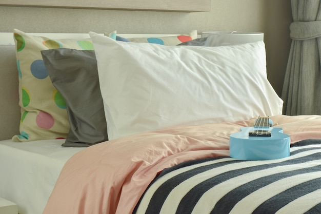 Ukulele azul claro na roupa de cama listrada