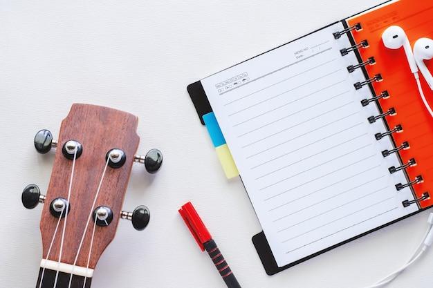 Ukulele com caderno espiral aberta, caneta e fones de ouvido no fundo branco