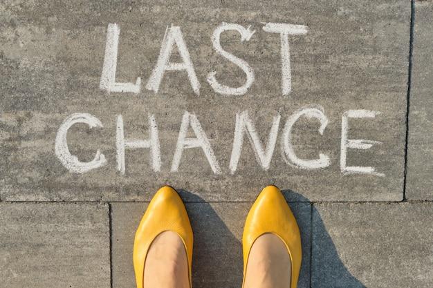 Última chance de texto escrita na calçada cinza com pernas de mulheres, vista superior