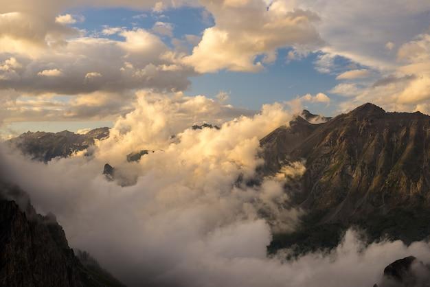Última luz solar quente no vale alpino, com picos de montanhas brilhantes e nuvens panorâmicas