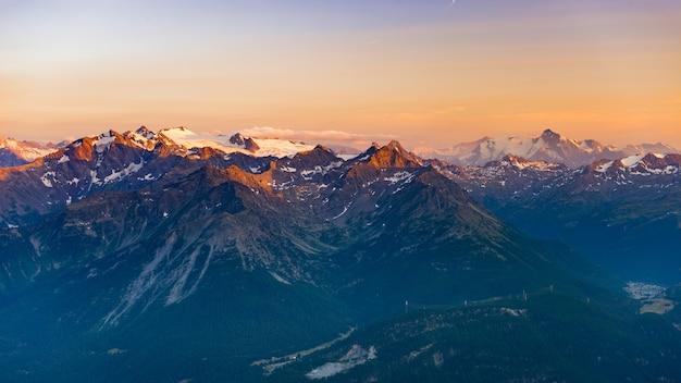 Última luz solar suave sobre picos rochosos, cumes e vales dos alpes ao nascer do sol.