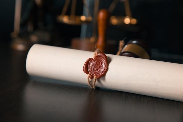 Última vontade e testamento em papel amarelado com martelo de juiz de madeira; documento é maquete