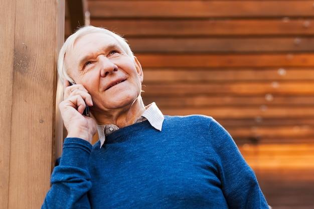 Último homem ao telefone. homem sênior feliz falando no celular e sorrindo enquanto fica ao ar livre