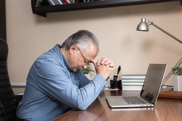 Último homem aprender a usar o computador. velho de vidro e camisa azul usando um laptop para estudar on-line em casa