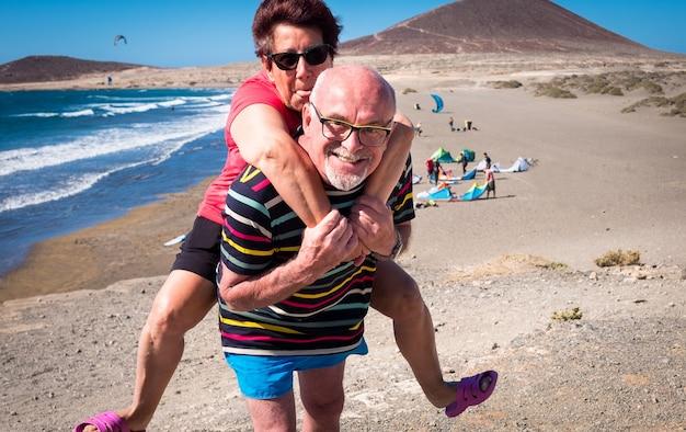 Último homem carrega sua esposa nos ombros. sorrisos e engraçado para a dificuldade. céu azul e mar com ondas como pano de fundo. praia e montanha