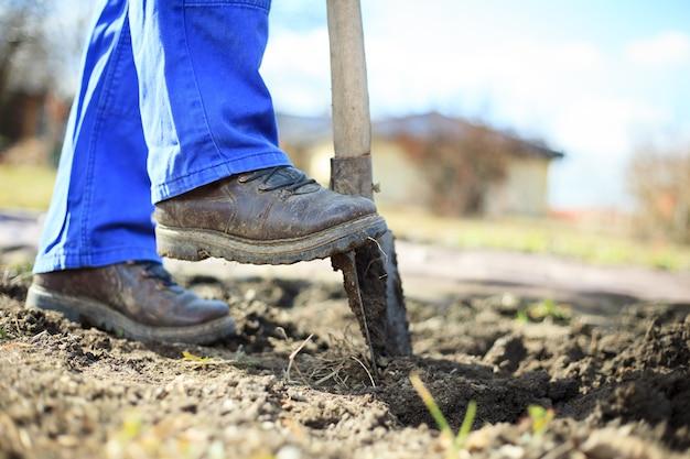 Último homem cavando um jardim para novas plantas após o inverno