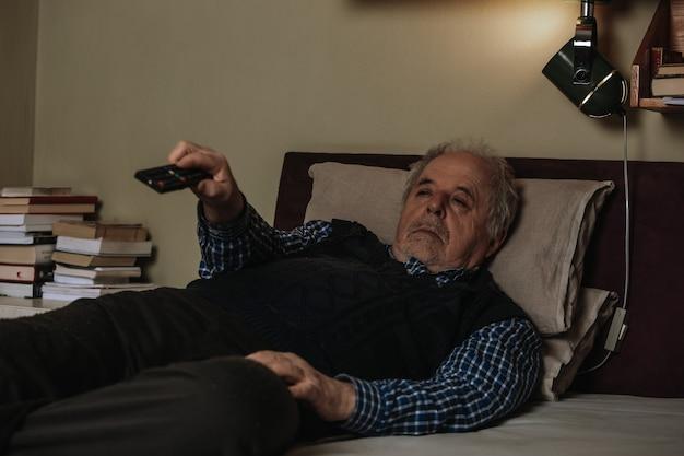 Último homem cochilando deitado na cama e assistindo tv com um controle remoto, descansando em uma cama