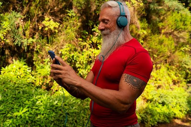 Último homem com barba branca correndo ao ar livre na natureza, segurando o telefone e escolhendo a música