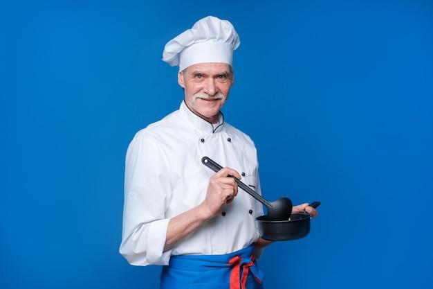 Último homem com barba cozinheiro com rosto animado em uniforme com concha