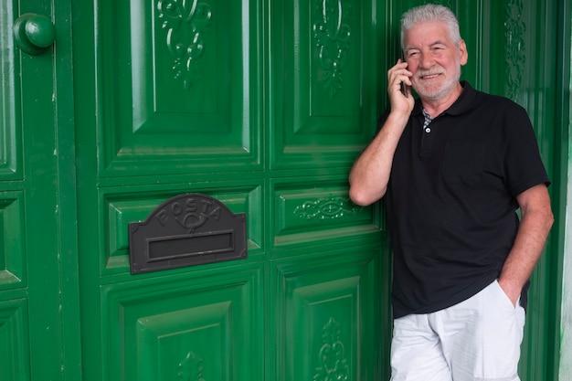 Último homem com barba e cabelo branco em pé e falando no celular. atrás dele, uma grande porta de madeira verde com a caixa de correio.
