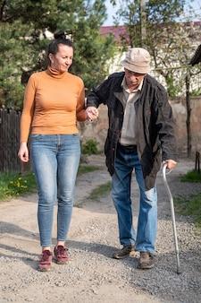 Último homem com bengala caminhando com a neta ao ar livre