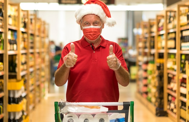 Último homem com chapéu de papai noel usando uma máscara protetora, empurrando o carrinho no supermercado