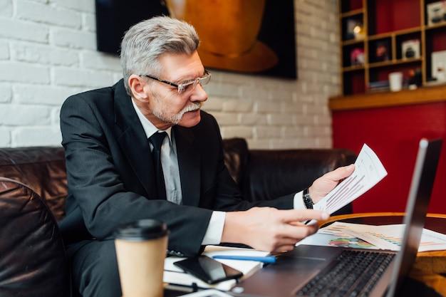 Último homem com uma xícara de café sentado na loja de um café moderno durante a hora do almoço, lendo jornais.