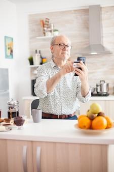 Último homem compras online usando smartphone e segurando o cartão de crédito durante o café da manhã na cozinha. idoso aposentado que usa o pagamento pela internet, compra do banco doméstico com tecnologia moderna
