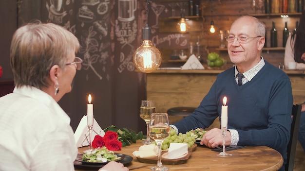 Último homem contando uma história interessante para sua adorável velhinha enquanto almoçava. feliz casal de velhos. aproveitando a aposentadoria.