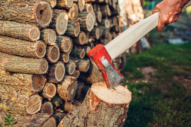 Último homem cortar lenha com um machado no pátio rural