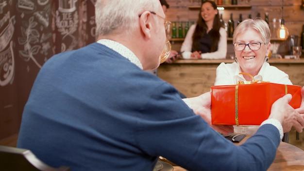 Último homem dando a sua esposa um presente de aposentadoria durante o jantar em um restaurante. homem e mulher alegres. adultos felizes.
