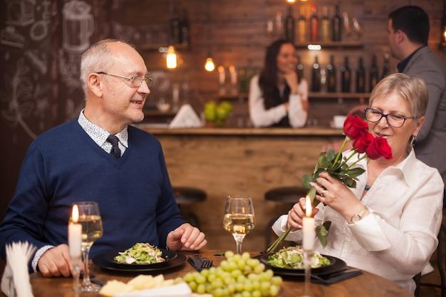 Último homem dando um buquê de flores para sua esposa. casal na casa dos sessenta. aproveitando a aposentadoria.